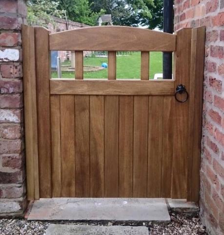 short brown garden side gate on between brick walls